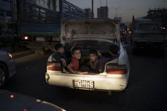 Afghan boys ride in the trunk of a car in Kabul, Afghanistan, Sunday, September 26, 2021. (Photo by Felipe Dana/AP Photo)