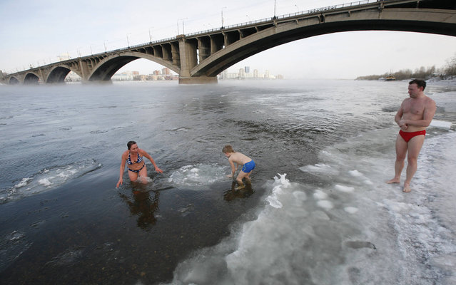 Daniil German (C), 9, a member of a local winter swimming club, goes for a dip in the Yenisei River at temperatures of about –24 degrees Celsius (–11 degrees Fahrenheit) in Russia's Siberian city of Krasnoyarsk, January 27, 2014. (Photo by Ilya Naymushin/Reuters)
