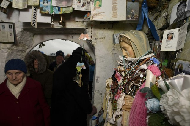 People queue to drink water from the holy well of St. Brigid and leave votive offerings on a Pattern Day pilgrimage to St. Brigid in Liscannor, Ireland February 1, 2017. (Photo by Clodagh Kilcoyne/Reuters)