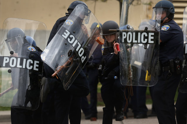 Baltimore Police officers protect themselves as protesters throw broken bricks at them outside the Mondawmin Mall following the funeral of Freddie Gray April 27, 2015 in Baltimore, Maryland. (Photo by Chip Somodevilla/Getty Images)