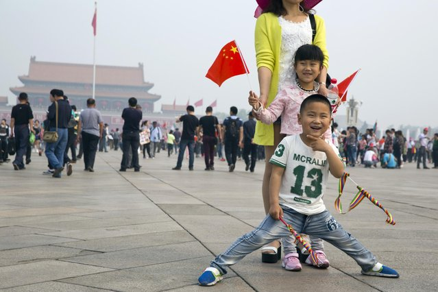 Visitors to Tiananmen Square pose for photos in Beijing, Friday, May 1, 2015. (Photo by Ng Han Guan/AP Photo)