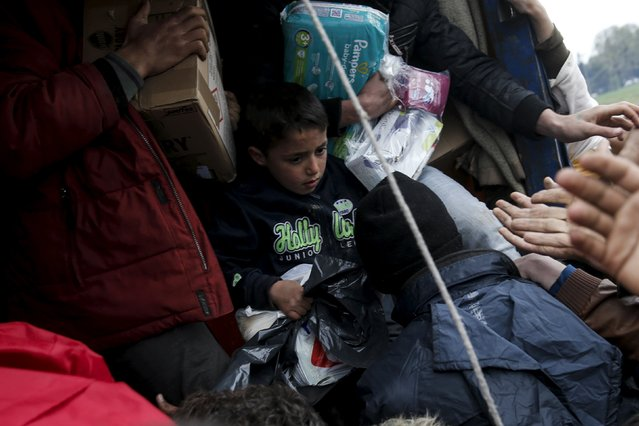 A boy holds a bag as refugees and migrants grab goods donated by volunteers from a truck at a makeshift camp at the Greek-Macedonian border, near the village of Idomeni, Greece March 16, 2016. (Photo by Alkis Konstantinidis/Reuters)