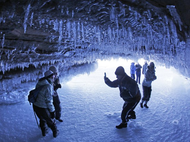 Visitors take pictures of each other in a cave at Apostle Islands National Lakeshore in northern Wisconsin. (Photo by Brian Peterson/AP Photo/Minneapolis Star Tribune)