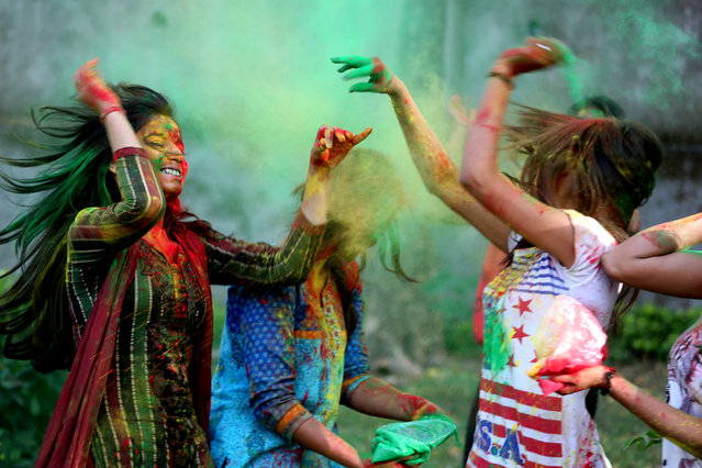 Indian college girls apply powdered color on each other's faces as they take part in Holi festival celebrations in Bhopal, India, March 20, 2016. (Photo by Sanjeev Gupta/EPA)