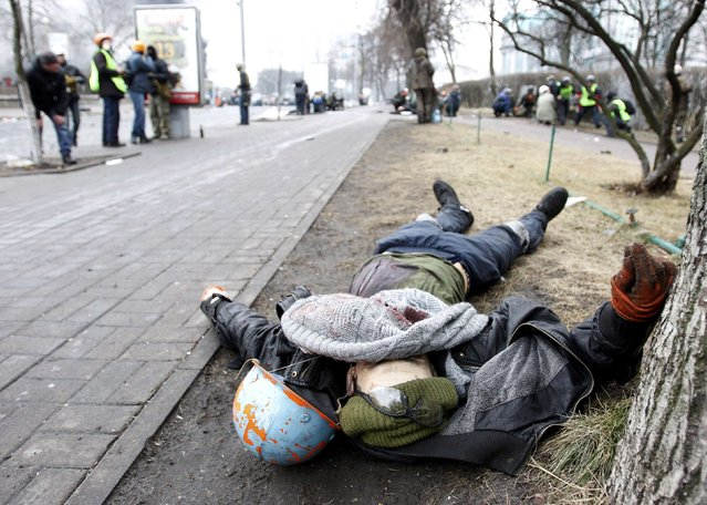 A dead body is seen on the ground after violence erupted in the Independence Square in Kiev February 20, 2014. Ukrainian protesters seized back Kiev's Independence Square in fresh clashes with riot police on Thursday that left several injured and possibly two demonstrators dead. (Photo by David Mdzinarishvili/Reuters)