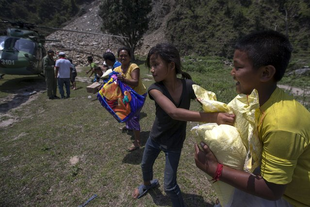 Earthquake survivors unload relief supplies from an Indian Army helicopter near Sirdibas, Nepal May 2, 2015. (Photo by Athit Perawongmetha/Reuters)