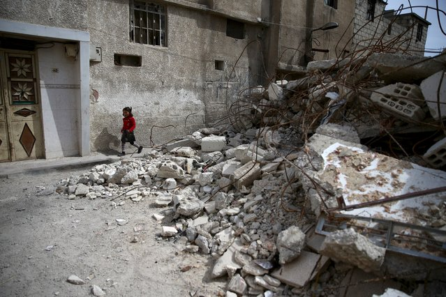 A girl walks near rubble of damaged buildings in the rebel held besieged town of Douma, eastern Damascus suburb of Ghouta, Syria March 19, 2016. (Photo by Bassam Khabieh/Reuters)