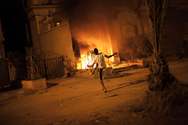 In this Sunday, June 30, 2013 file photo, an Egyptian protester attacks Muslim Brotherhood headquarters in Muqattam district in Cairo. Egypt's top prosecutor on Sunday, March 29, 2015 has named 18 Muslim Brotherhood members, including leader Mohammed Badie and his deputy Khairat el-Shater, as terrorists in the first implementation of an anti-terror law passed earlier this year. (Photo by Manu Brabo/AP Photo)