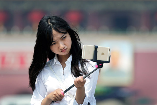 A woman reacts as she uses a selfie stick to take a photo of herself at Tiananmen Square in Beijing, China, Thursday, April 30, 2015. Selfie sticks are gaining popular in China, and many people are using them at popular tourist destinations. (Photo by Andy Wong/AP Photo)