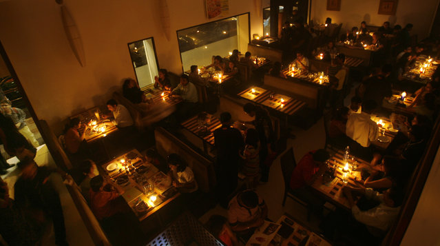People dine in candlelight at a restaurant during Earth Hour in Mumbai March 28, 2009. (Photo by Arko Datta/Reuters)