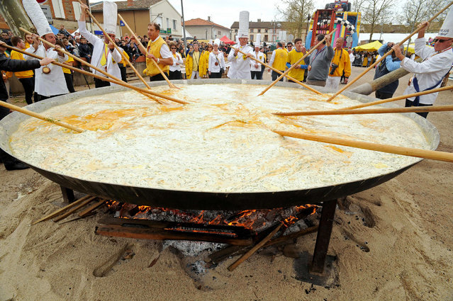 Members of the Giant Omelette Brotherhood of Bessieres cook a giant omelette as part of Easter celebrations on March 28, 2016, on the main square of Bessieres, southern France. Over 15,000 eggs were used to make the omelette. (Photo by Remy Gabalda/AFP Photo)