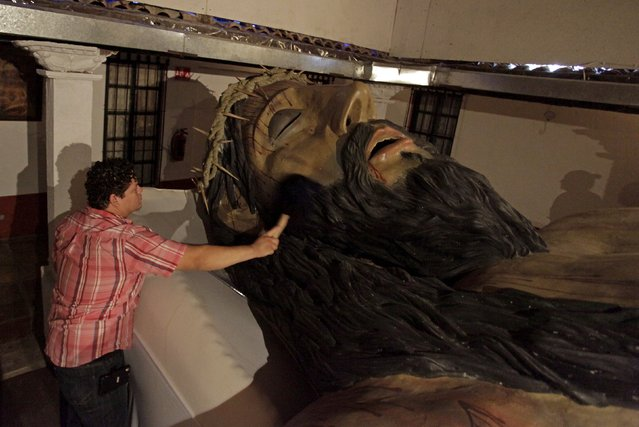 A man brushes dust off a wooden sculpture of Christ at his home in Montemorelos, Nuevo Leon state, May 15, 2015. The wooden sculpture, 12 metres in length and weighing more than three tons, was built by a family of sculptors, local media reported. The Santiesteban family started making the sculpture in August 2003 and completed the work on December 2014, and it is located in their backyard for visitors to view. (Photo by Daniel Becerril/Reuters)