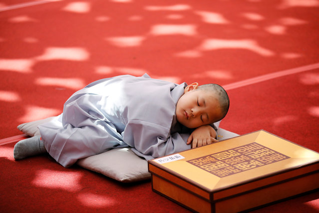 A novice monk naps after getting his head shaved by a Buddhist monk during an event to celebrate the upcoming Vesak Day, birthday of Buddha, at Jogye temple in Seoul, South Korea, April 22, 2019. (Photo by Kim Hong-Ji/Reuters)