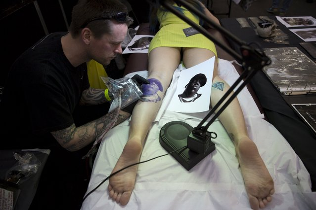 A woman is tattooed during the Great British Tattoo Show in Alexandra Palace in north London, Britain May 23, 2015. (Photo by Neil Hall/Reuters)