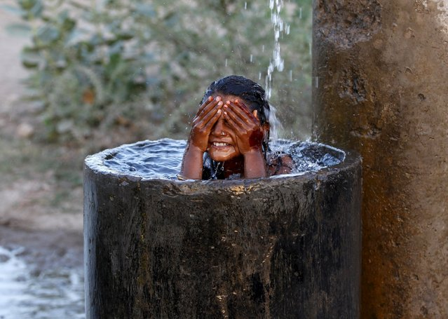 A girl bathes to cool off herself with water that is leaking from a broken pipe valve on a hot summer day on the outskirts of Ahmedabad, India, May 18, 2015. (Photo by Amit Dave/Reuters)