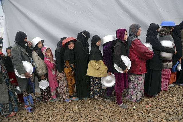 Displaced Iraqis, who fled fighting between Iraqi security forces and Islamic State militants, line up to receive  food, at a camp for internally displaced people, in Hamam al-Alil, some 10 kilometers south of Mosul, Iraq, Thursday, March 2, 2017. (Photo by Khalid Mohammed/AP Photo)