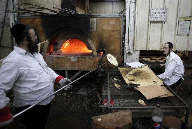 Ultra-Orthodox Jewish men prepare matza, traditional unleavened bread eaten during the upcoming Jewish holiday of Passover, in the southern city of Ashdod April 17, 2016. (Photo by Amir Cohen/Reuters)