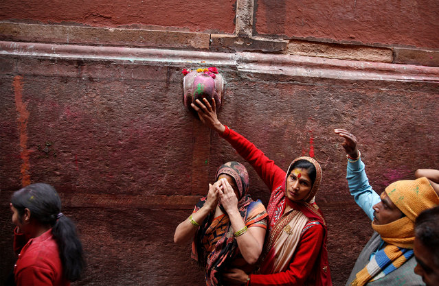 A Hindu devotee touches the outside of a temple as she takes part in the religious festival of Holi in Vrindavan, in the northern state of Uttar Pradesh, India, March 8, 2017. (Photo by Cathal McNaughton/Reuters)