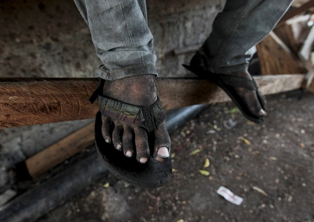 The feet of a worker are pictured at a traditional charcoal factory at a village in Nagarote town, Nicaragua, May 28, 2015. Around 300 families live off the sale of charcoal in this area located in the dry corridor of Nicaragua. Friday marks World Environment Day. Picture taken May 28, 2015. REUTERS/Oswaldo Rivas