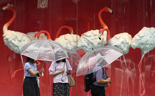 People walk in the rain through a shopping area Monday, July 1, 2019, in Tokyo. (Photo by Eugene Hoshiko/AP Photo)