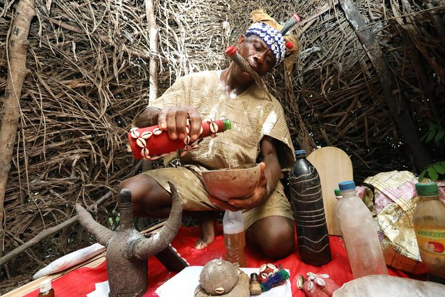 Chief Baykuh, a traditional healer in his shrine at Magbumoh village mixes herbs into potions on December 1, 2018. In his mouth he holds an animal horn called a ke'elen which is used to communicate with the gods who guide him. (Photo by Lynn Rossi/AFP Photo)