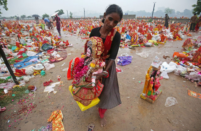 """A woman carries an idol of Hindu goddess Dashama, left by devotees on the banks of the river Sabarmati a day after the """"Dashama"""" festival in Ahmedabad, India, August 11, 2019. (Photo by Amit Dave/Reuters)"""