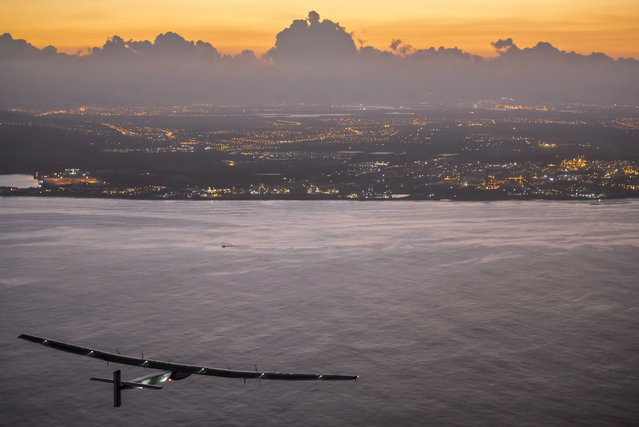 In this photo provided by Jean Revillard, Solar Impulse 2, a plane powered by the sun's rays and piloted by Andre Borschberg, approaches Kalaeloa Airport near Honolulu, Friday, July 3, 2015. (Photo by Jean Revillard/Global Newsroom via AP Photo)