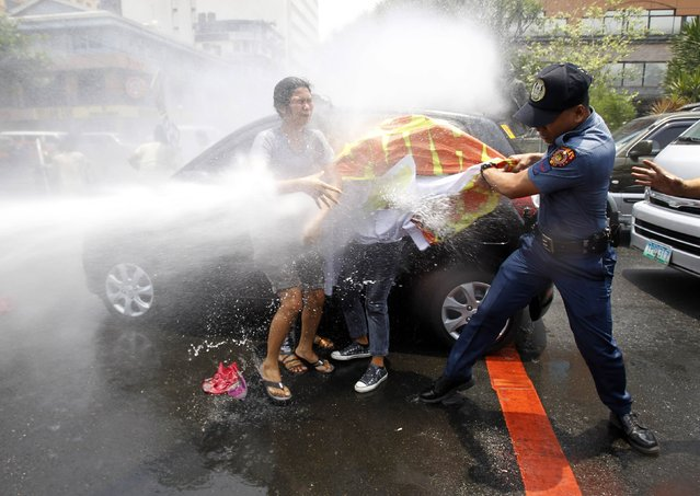 An anti-riot policeman grabs a banner from protesters as they are hit with a water cannon during a protest against the upcoming visit of U.S. President Barack Obama next week, in front of the U.S. embassy in Manila April 23, 2014. (Photo by Romeo Ranoco/Reuters)