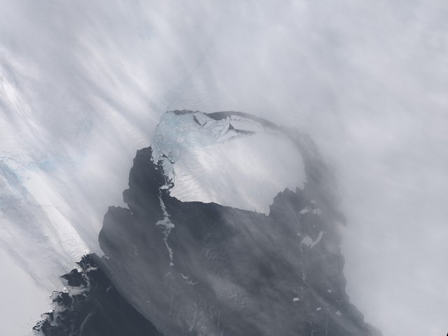 The B-31 Iceberg is seen after separating from a rift in Antarctica's Pine Island Glacier in this NASA Earth Observatory handout image acquired on November 13, 2013. Scientists are monitoring an unusually large iceberg - roughly six times the size of Manhattan – that broke off from an Antarctic glacier and is heading into the open ocean, although not in an area heavily navigated by ships. (Photo by Holli Riebeek/Reuters/NASA Earth Observatory)