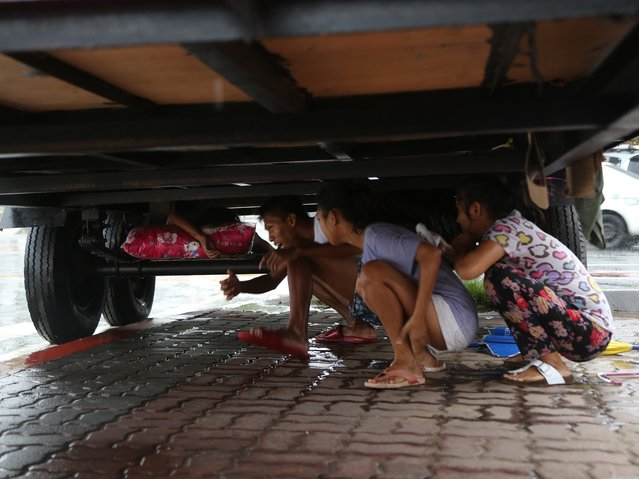 Filipinos take cover from the rain underneath a container van as Tropical Storm Linfa enhanced the southwest monsoon in Manila, Philippines on Sunday, July 5, 2015. Tropical Storm Linfa blew across northern Philippines' causing floods and knocking out power in several towns in provinces. (Photo by Aaron Favila/AP Photo)