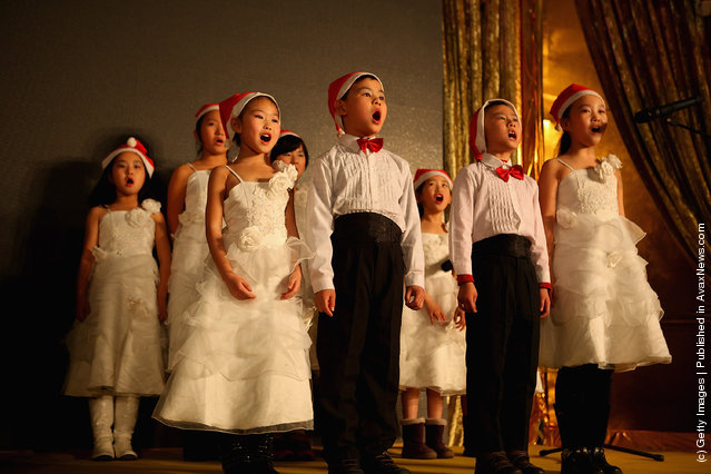 Chinese children sing Christmas songs for customers at a shopping center on Christmas Eve