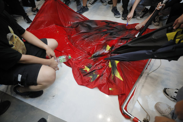 Protesters vandalize a Chinese national flag during a protest at a mall Sunday, September 22, 2019, in Hong Kong. Hong Kong's pro-democracy protests, now in their fourth month, have often descended into violence in the evenings. A hardcore group of the protesters says the extreme actions are needed to get the government's attention. (Photo by Kin Cheung/AP Photo)
