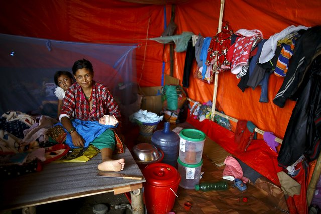 An earthquake victim sits with her baby girl, who was born nine days ago, inside their makeshift shelter in Kathmandu, Nepal July 8, 2015. Two months after massive twin earthquakes killed 8,897 people in Nepal, nearly three million survivors, many in mountainous, hard-to-reach areas, still needed shelter, food and basic medical care as the yearly monsoon bore down on the Himalayan nation, the U.N. said in a report released last week. (Photo by Navesh Chitrakar/Reuters)