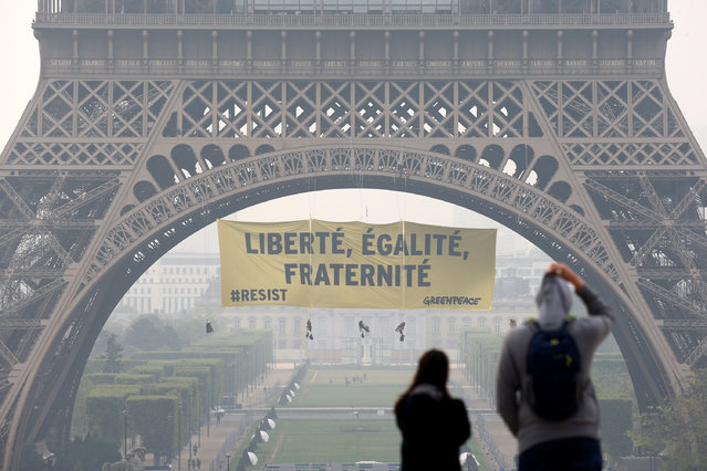 "Tourists walk at Trocadero square as activists from the environmentalist group Greenpeace unfurl a giant banner on the Eiffel Tower which reads ""Liberty, Equality, Fraternity"" in a call on French citizens to vote against the National Front (FN) presidential candidate Marine Le Pen, in Paris, France May 5, 2017. (Photo by Gonzalo Fuentes/Reuters)"