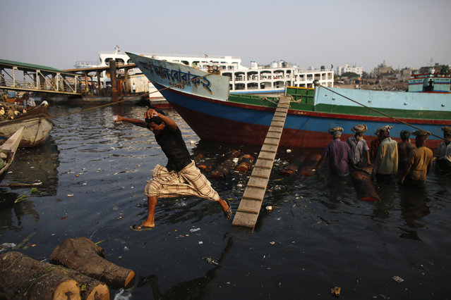 A man jumps off from a boarding ramp to a boat near a timber factory by the river Buriganga in Dhaka May 18, 2014. (Photo by Andrew Biraj/Reuters)