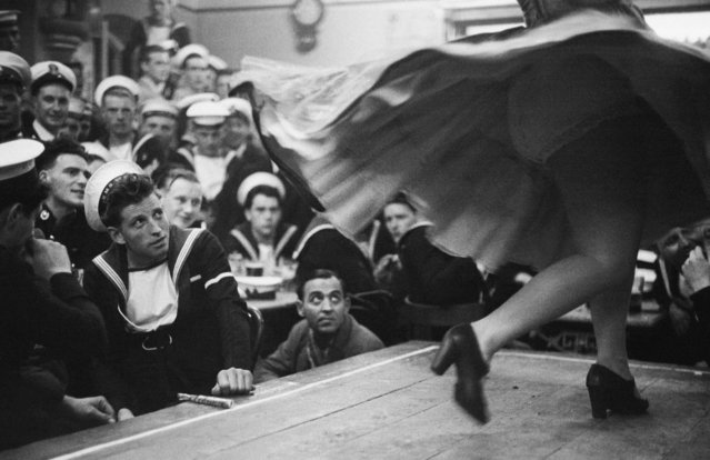 British sailors taking shore leave on the British dependency of Gibraltar visit the Suiza Bar to watch a Spanish dancer perform on August 05, 1954. These Spanish entertainers are under contract and must return over the border by 11 o'clock. (Photo by Bert Hardy/Getty Images)