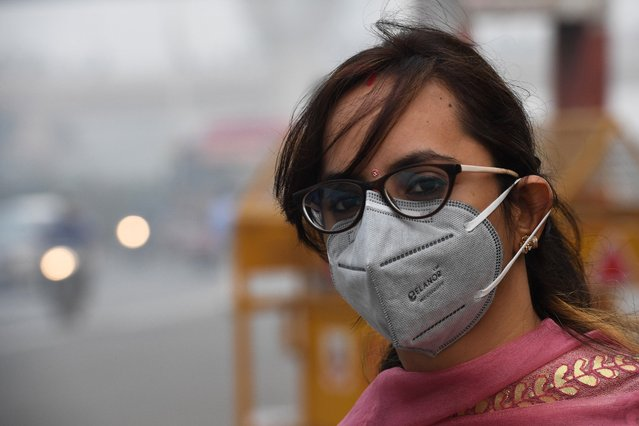 "A woman wearing a protective face mask waits for public bus in smoggy conditions in New Delhi on November 4, 2019. Millions of people in India's capital started the week on November 4 choking through ""eye-burning"" smog, with schools closed, cars taken off the road and construction halted. (Photo by Prakash Singh/AFP Photo)"