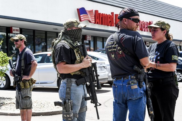 A small group of armed citizens stand guard outside a Colorado Springs, Colo.,  Armed Forces Career Center Wednesday, July 22, 2015. Gun-toting citizens are showing up at military recruiting centers around the country, saying they plan to protect recruiters following last week's killing of four Marines and a sailor in Chattanooga, Tenn. (Photo by Michael Ciaglo/The Gazette via AP Photo)