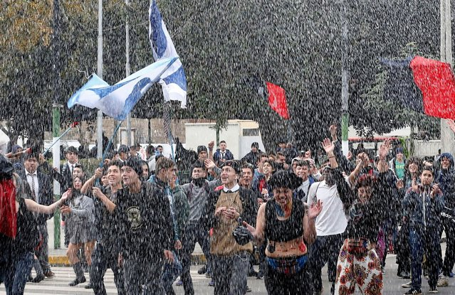 Demonstrators shout slogans as a riot police vehicle releases a jet of water during an unauthorized march called by secondary students to protest against government education reforms in Valparaiso, Chile, May 26, 2016. (Photo by Rodrigo Garrido/Reuters)