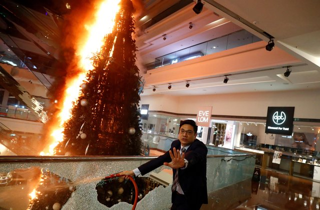 A man reacts as he tries to extinguish a burning Christmas tree at Festival Walk mall in Kowloon Tong, Hong Kong, November 12, 2019. Anti-government protesters smashed windows and set fires in the mall on Tuesday, including to a big Christmas tree. (Photo by Thomas Peter/Reuters)