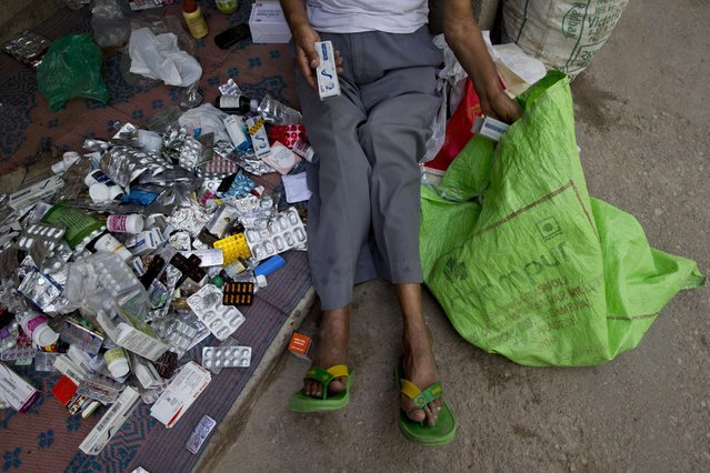 """In this June 8, 2015 photo, Omkarnath, who goes by the name """"Medicine Baba"""", sorts out unused medicines donated by people to weed out the expired and used medicines in New Delhi, India. (Photo by Saurabh Das/AP Photo)"""