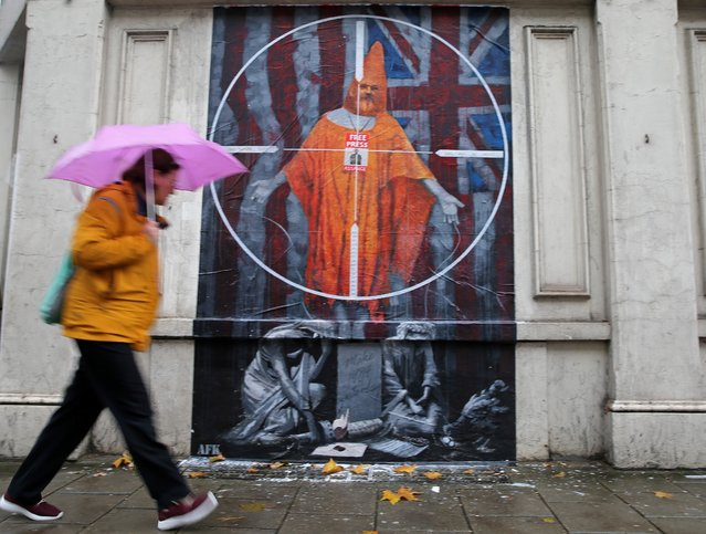 A pedestrian passes a graffiti mural of WikiLeaks founder Julian Assange, near Westminster Magistrates Court in London on October 21, 2019, ahead of a case management hearing in Assange's case. WikiLeaks founder Julian Assange was ordered Friday to make his first in-person London court appearance to determine whether he can be released from prison as he fights extradition to the United States. The 48-year-old Australian has been in custody at the high-security Belmarsh prison in southwest London since being dramatically dragged from Ecuador's embassy in April. (Photo by Isabel Infantes/AFP Photo)