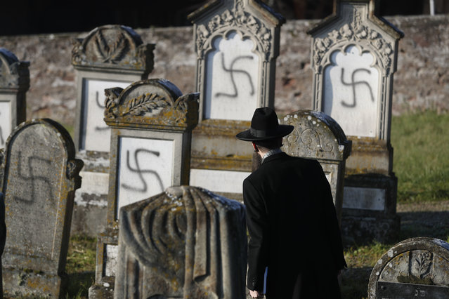 Strasbourg chief Rabbi Harold Abraham Weill watches vandalized tombs in the Jewish cemetery of Westhoffen, west of the city of Strasbourg, eastern France, Wednesday, December 4, 2019. Regional authorities in eastern France say vandals have scrawled anti-Semitic inscriptions, including swastikas spray-painted in black, on 107 tombs in a Jewish cemetery. (Photo by Jean-Francois Badias/AP Photo)