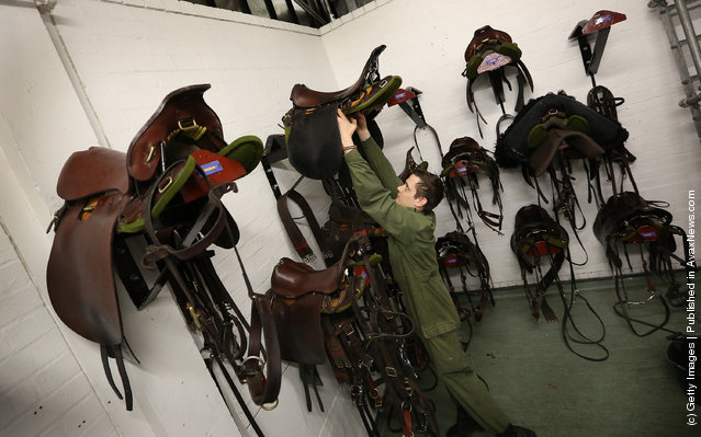 Trooper Marc Goodwin of The Household Cavalry Mounted Regiment (HCMR) lifts a saddle down from the wall in the tack room at Hyde Park Barracks