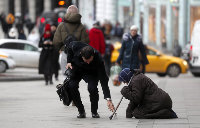 A beggar woman begs for alms on Tverskaya street in downtown of Moscow, Russia, 20 November 2019. (Photo by Maxim Shipenkov/EPA/EFE)