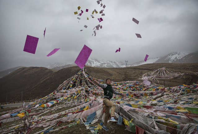 A Tibetan man throws prayers in the air at a high altitude pass on May 22, 2016 on the Tibetan Plateau near Yushu town in the Yushu Tibetan Autonomous Prefecture of Qinghai province. (Photo by Kevin Frayer/Getty Images)