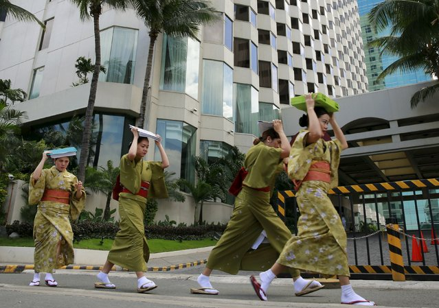 Hotel employees wearing Kimonos evacuate from a building as they participate in the simultaneous earthquake drill in Manila July 30, 2015.. (Photo by Romeo Ranoco/Reuters)