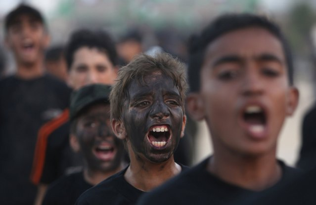 "Young Palestinians shout slogans during a military-style exercise at the Liberation Youths summer camp organised by the Hamas movement, in Rafah in the southern Gaza Strip August 1, 2015. Hamas stages dozens of military-style summer camps for young Palestinians in the Gaza Strip to prepare them to ""confront any possible Israeli attack"", organisers said. (Photo by Ibraheem Abu Mustafa/Reuters)"