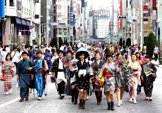 Kimono-clad high school students and local people from Isesaki city of Gunma Prefecture, march at Tokyo's Ginza dstrict on June 22, 2014, to commemorate the addition of the Tomioka Silk Mill and its related sites in the prefecture to the list of World Heritage sites. About 80 local people wore Meisen silk kimono, a special product of Isesaki, where Tajima Yahei Sericulture Farm, has been listed as one of the Tomioka Silk Mill related sites. (Photo by AFP Photo/The Yomiuri Shimbun)