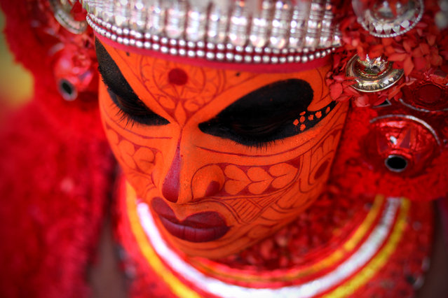 """Theyyam"". Preparation for the Theyyam performance in the surroundings of Kasaragod city. Theyyam is a popular ritual dance form of North Kerala, particularly in Kannur and Kasargod districts. The Theyyam represents a mythological, divine or heroic character. Make up of Theyyams is done by specialist. There are different types of face painting for which primarily and secondary colours are used. Photo location:  Kasaragod, India. (Photo and caption by Rafal Ziejewski/National Geographic Photo Contest)"